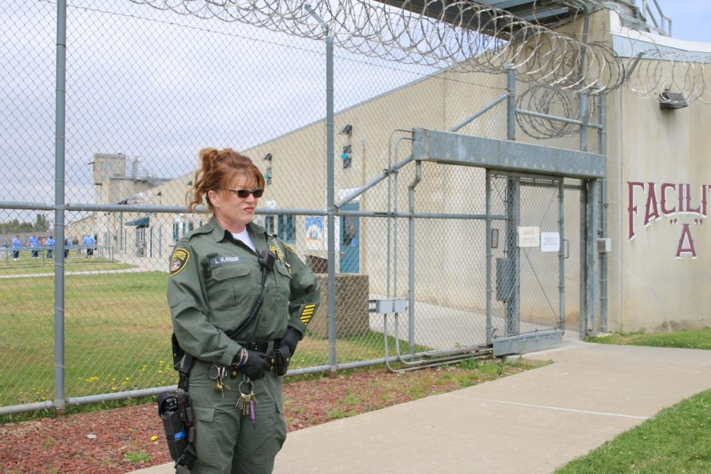 Woman in uniform looks out over prison yar.d.