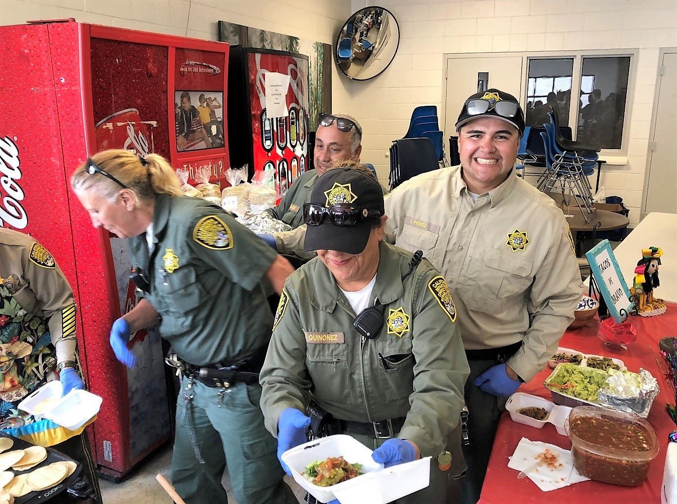 People in uniform load up tacos.