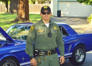 Man in uniform leans against sports car.