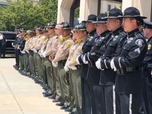 People in uniforms stand at attention in a line.