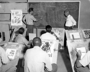Two men at a chalkboard while others sit in desks and watch.