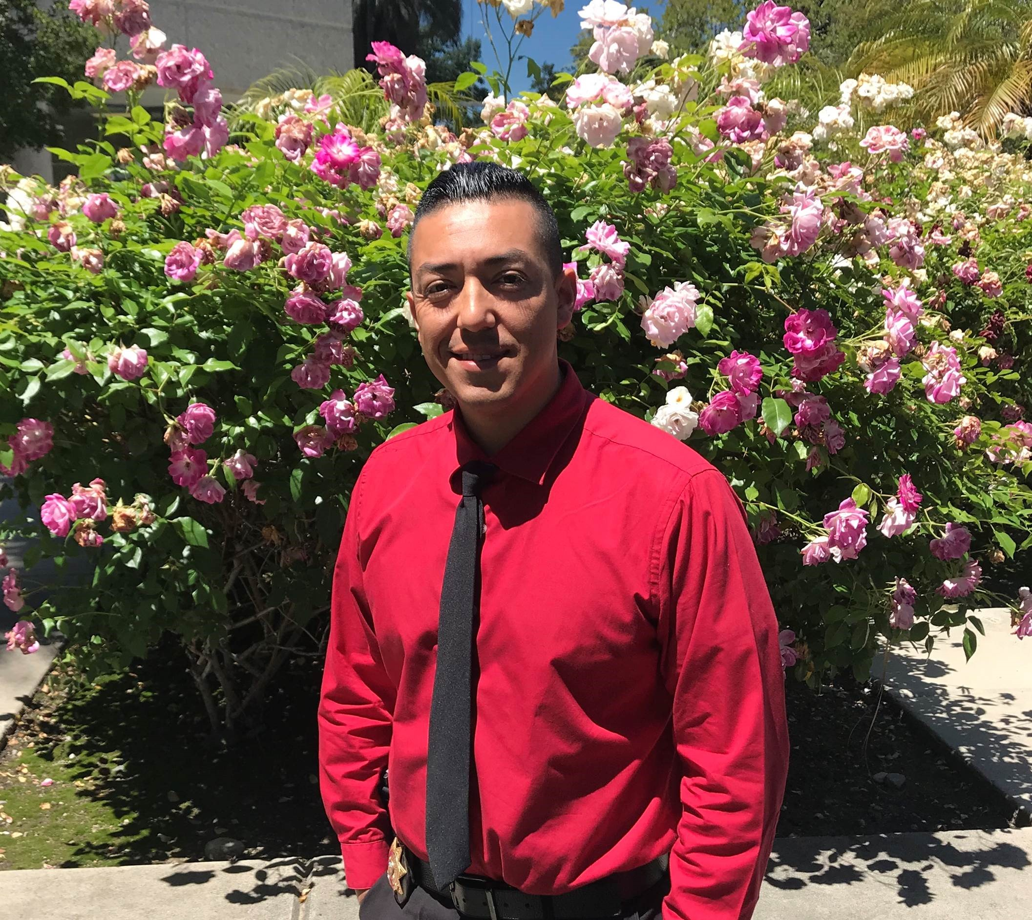 Man in red shirt and dark tie stands in front of rose bushes.