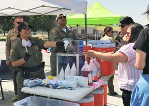 Woman in uniform serves another woman a snow cone.