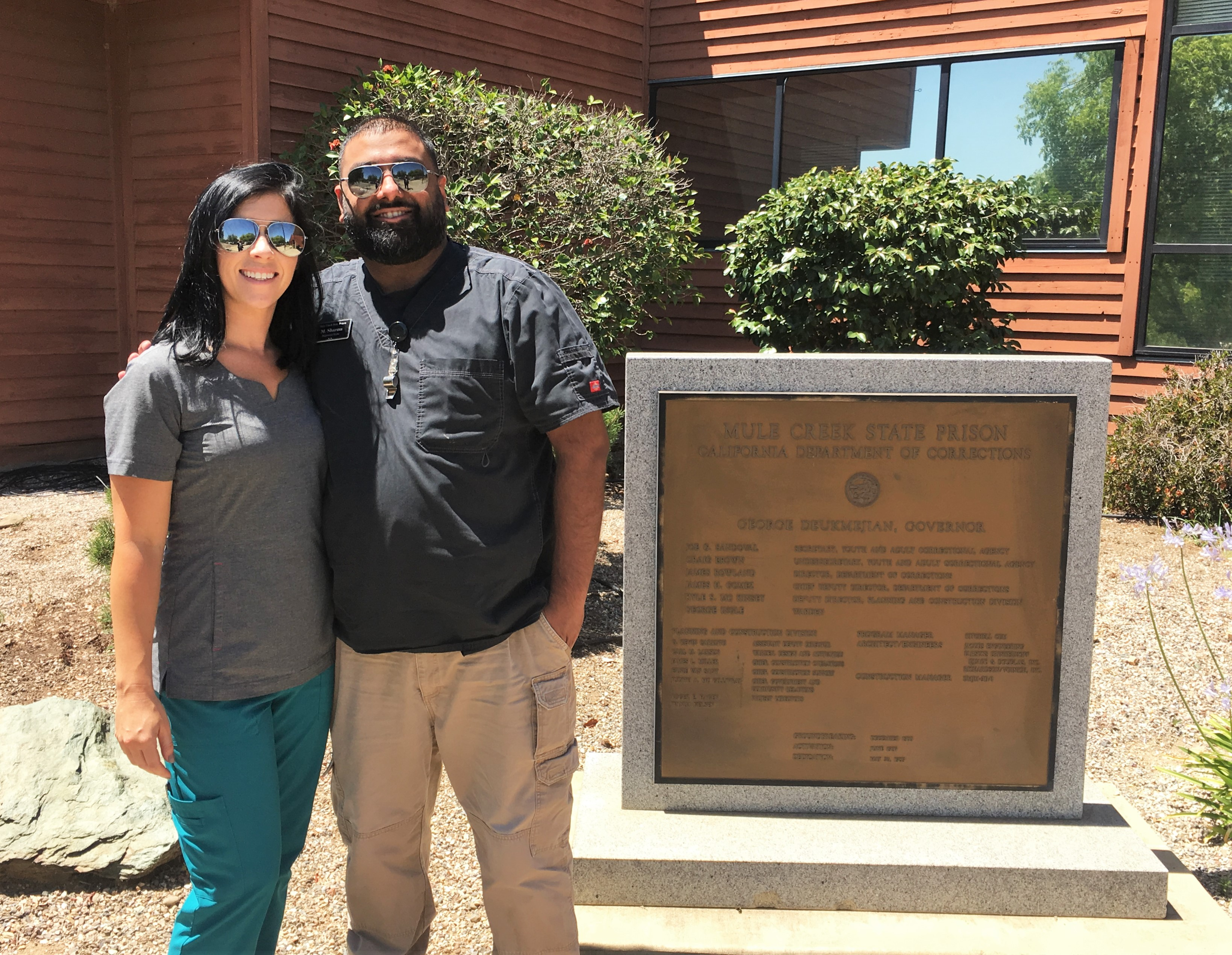Woman in scrubs and man in regular clothing stand in front of the plaque for Mule Creek State Prison.