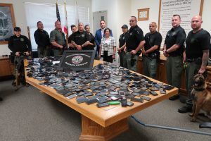 People and police dogs stand around a table full of cell phones.