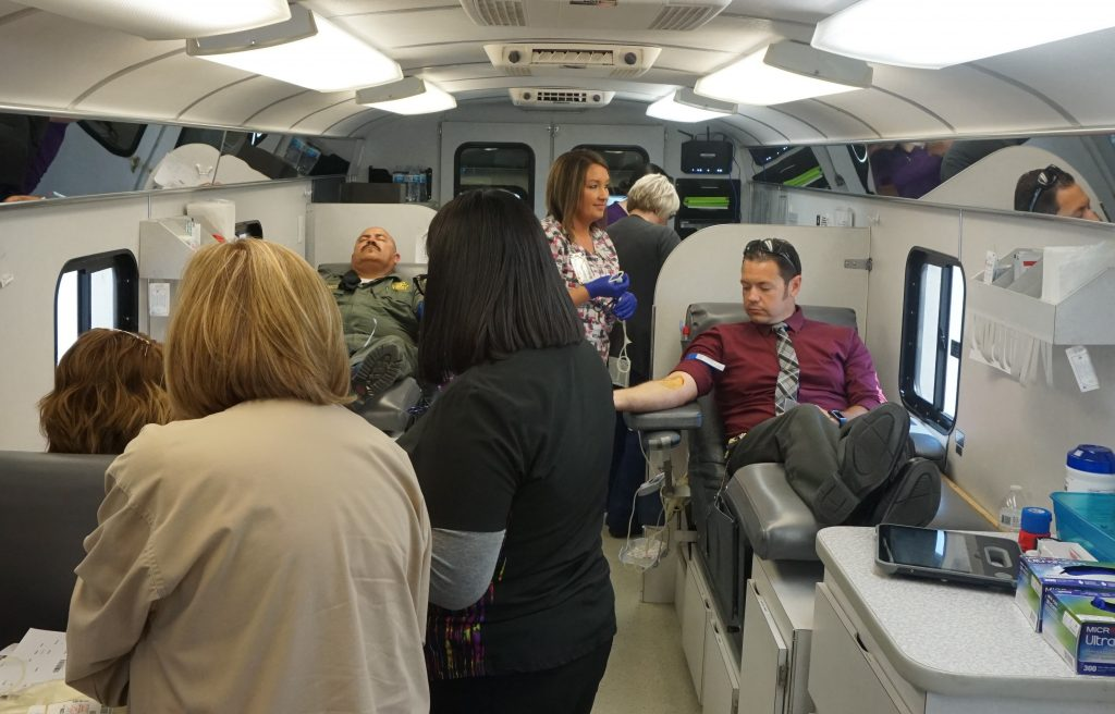 People donate blood in a large vehicle.