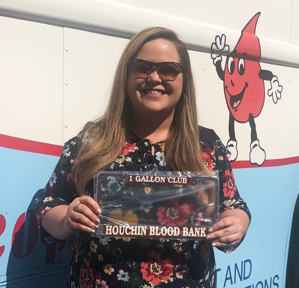 Lady holds a license plate frame because she donated one gallon of blood.