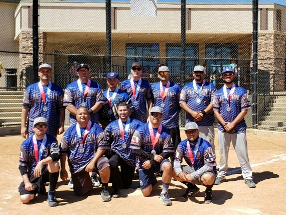 People wear matching shirts with medals around their necks.