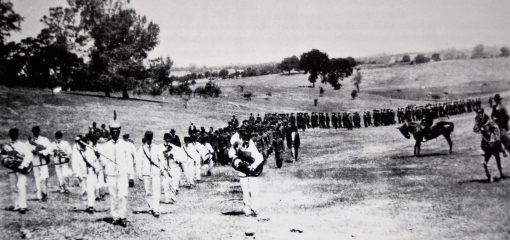 Boys in white band uniforms playing instruments march in front of others along hillsides while two men on horseback look on.