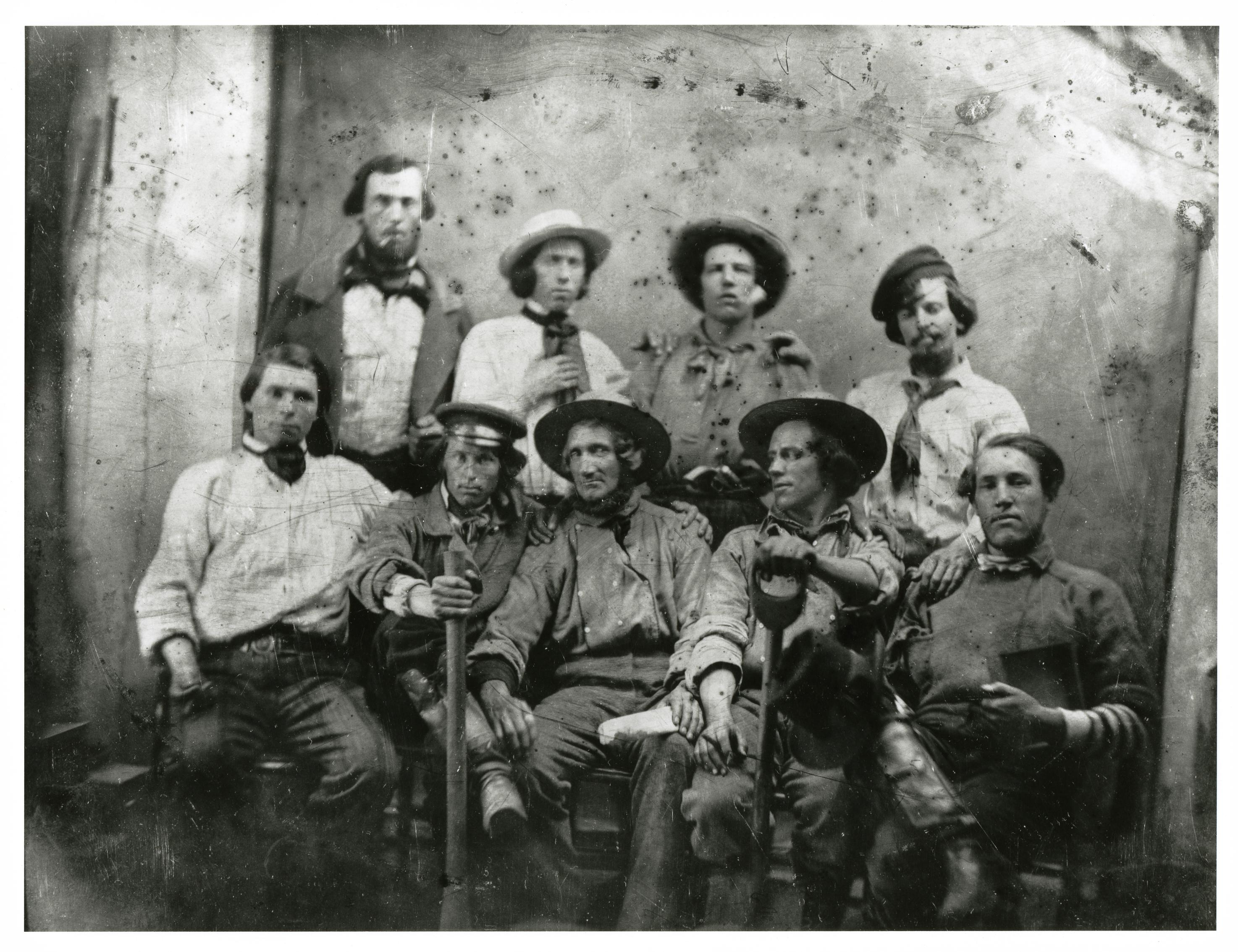 Men with shovels and dirty clothing pose for a photo.