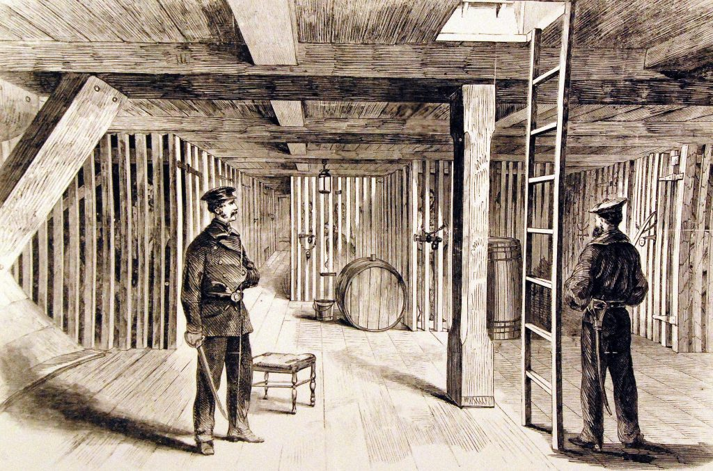 Guards stand outside cells below deck.