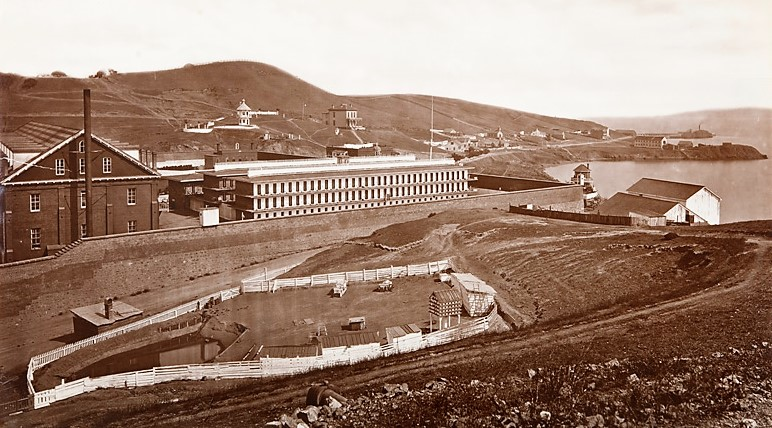 Prison building behind a pasture.