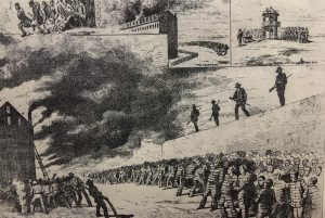 Men in uniform stand atop a wall while men in striped outfits back away from smoke.