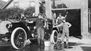 Three men stand behind a fire engine that appears to have been recently washed as a water bucket is nearby.