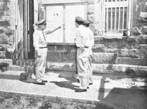Three uniformed men stand in front of a brick wall with flyers on a board. One man points to them.