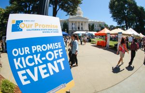 Sign says Our Promise Kick-Off Event while people walk around at the state capitol.