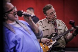 As music therapy, a man in blue shirt sings in microphone while correctional officer plays guitar.