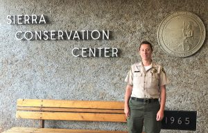 Woman in correctional officer uniform stands in front Sierra Conservation Center sign.