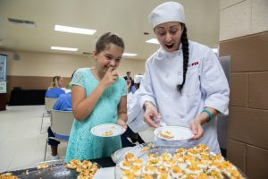 Woman in chef's clothing and young girl sample food.