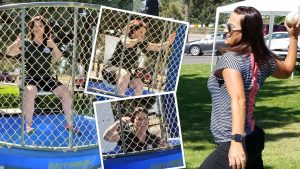 Woman throws softball at a dunk tank, as another woman drops into the water.