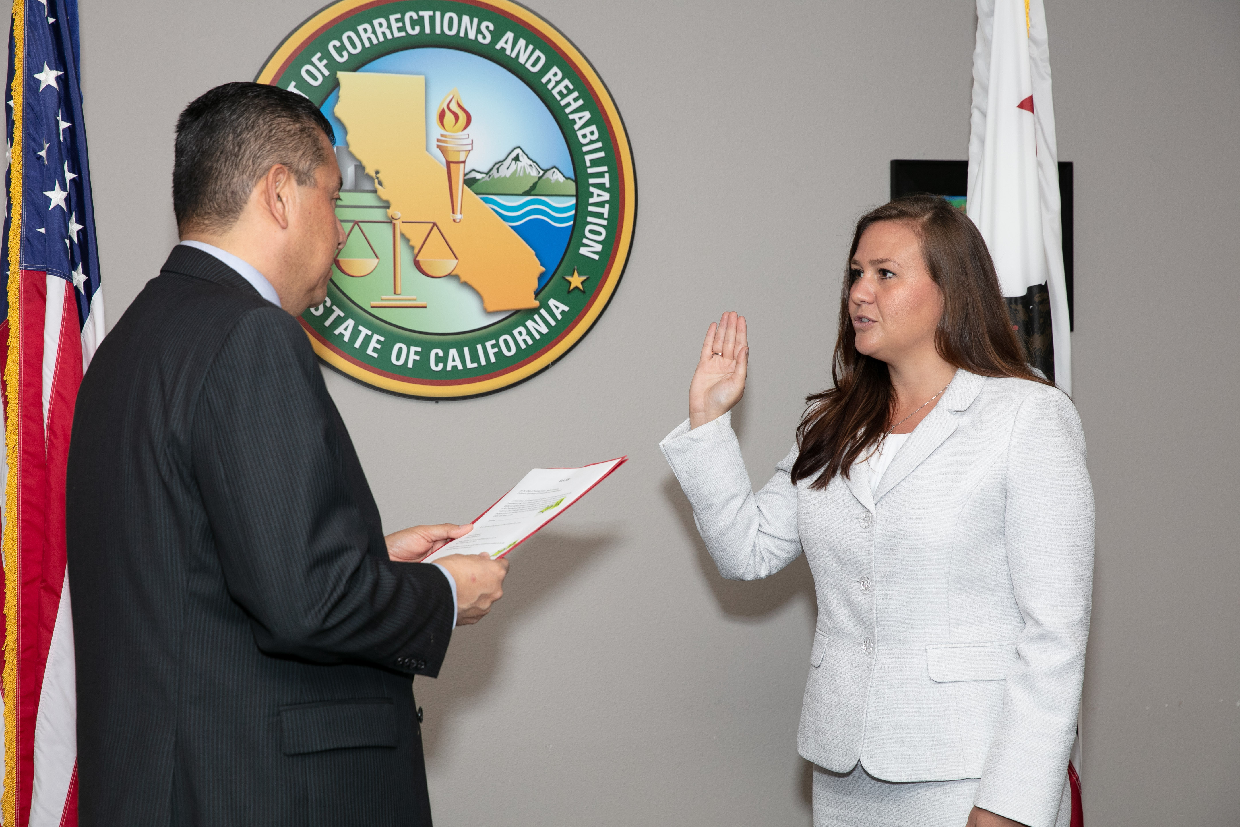 Woman raises right hand while man in suit reads from paper.