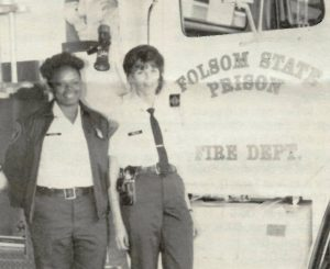 Two women in uniform stand beside a truck with the words Folsom State Prison Fire Dept.