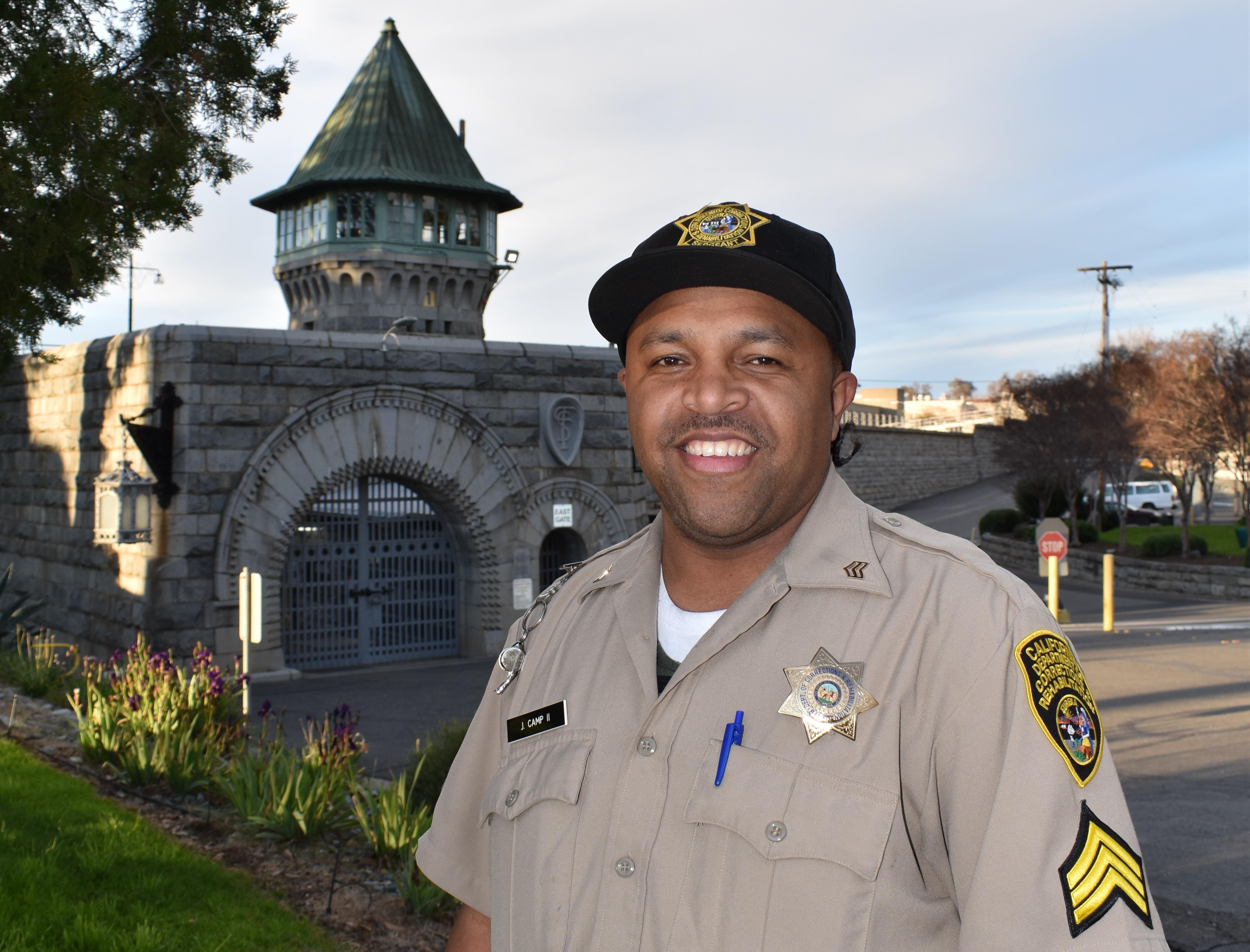 Uniformed man stands in front of gothic stone wall and tower.