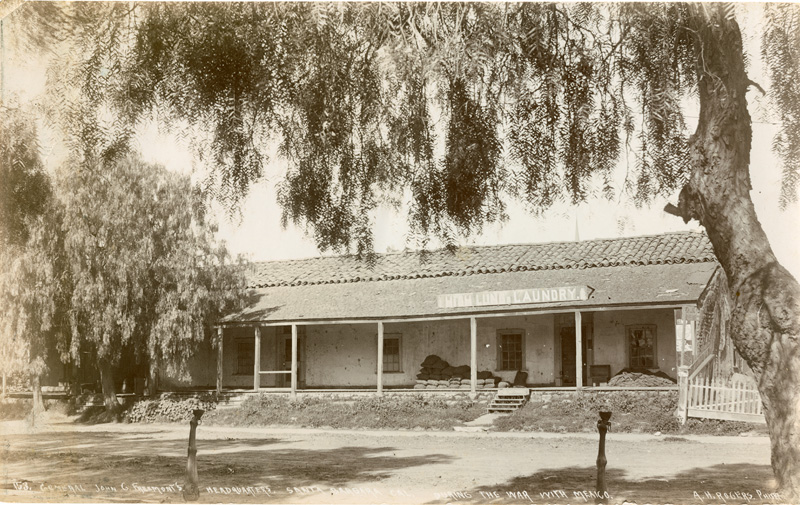 """Old adobe building with sign that says """"laundry."""""""