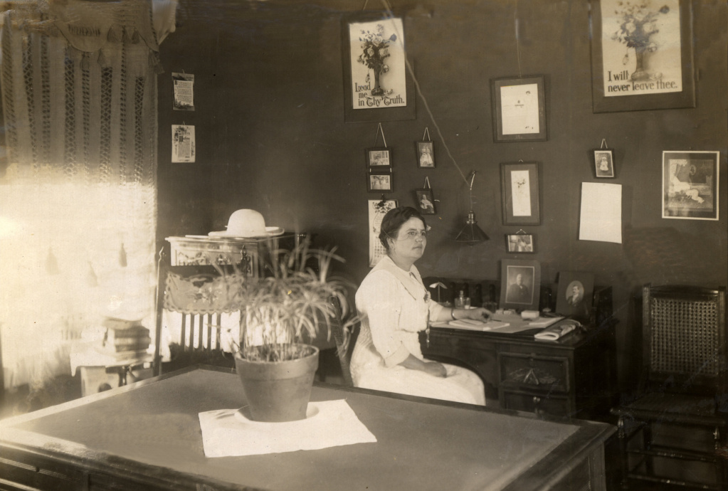 Woman wearing large white dress sits behind a desk.