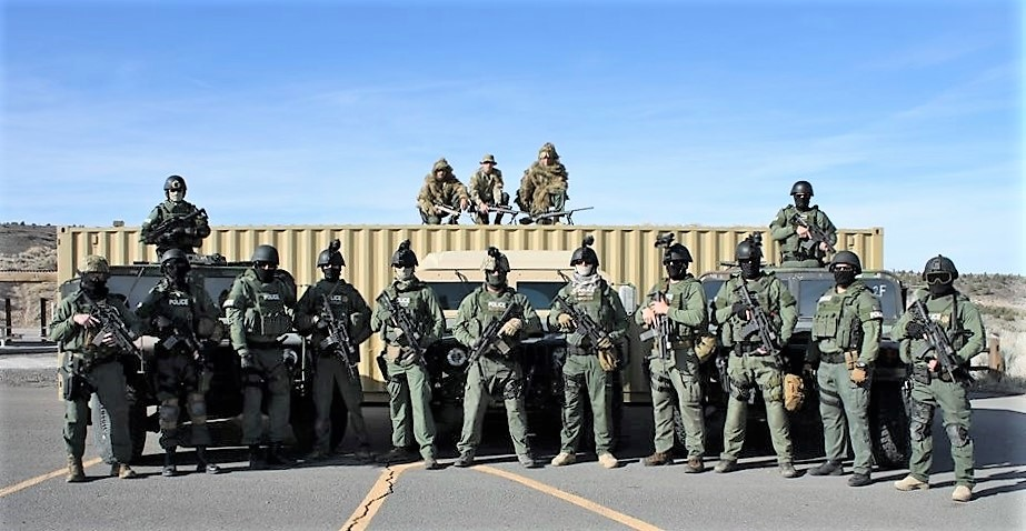 People in uniform hold guns.