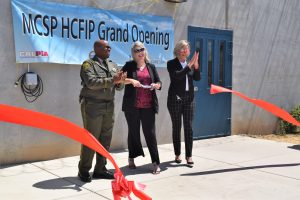 A man in uniform and two women cut a big red women in front of a banner that says MCSP HCFIP Grand Opening.