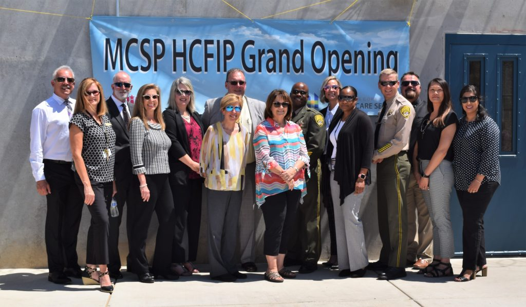 A group stands in front of a building with a banner that says MCSP MCFIP Grand Opening.