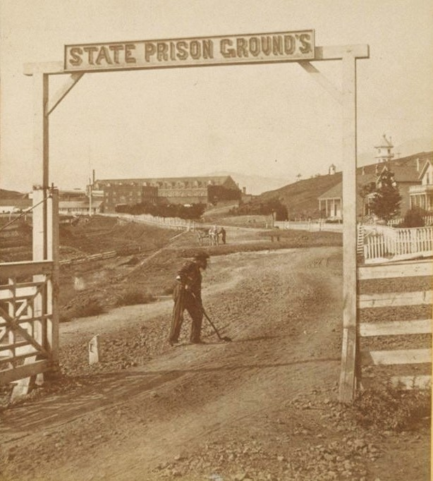 Man in striped prison clothing works under a sign that reads State Prison Grounds.