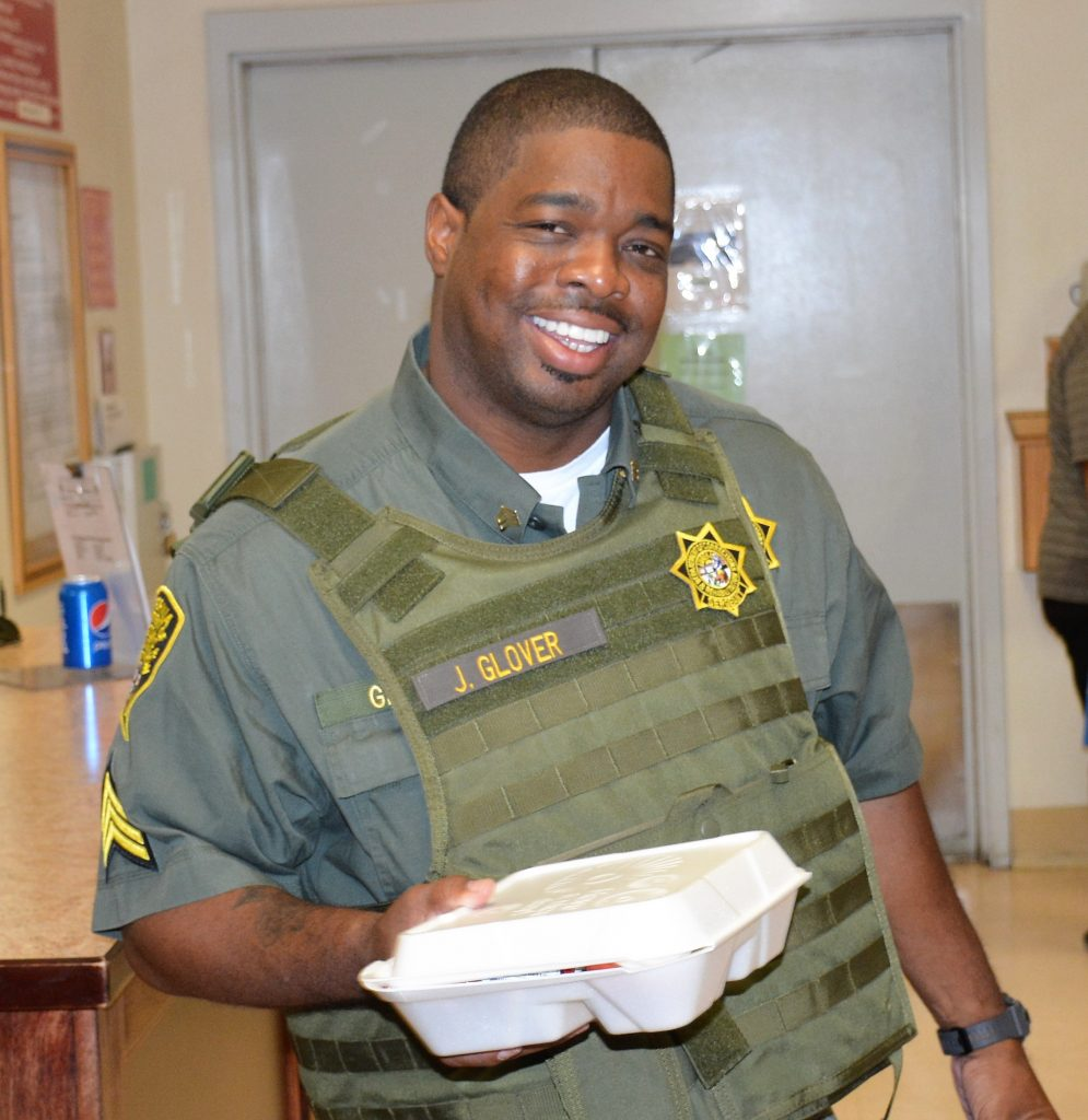 Man in uniform and protective vest smiles while holding a box lunch.