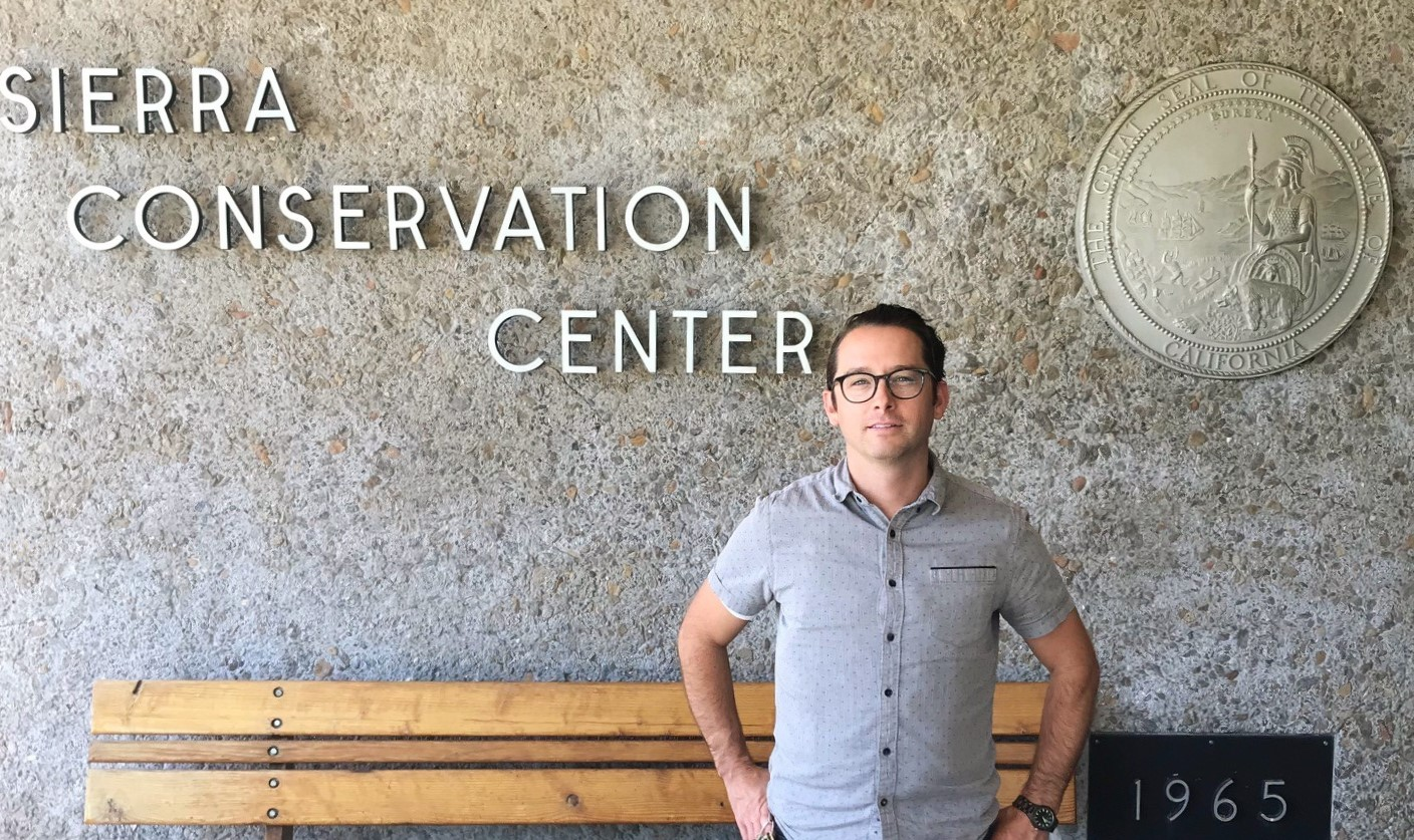Man stands in front of Sierra Conservation Center prison, with hands on hips.