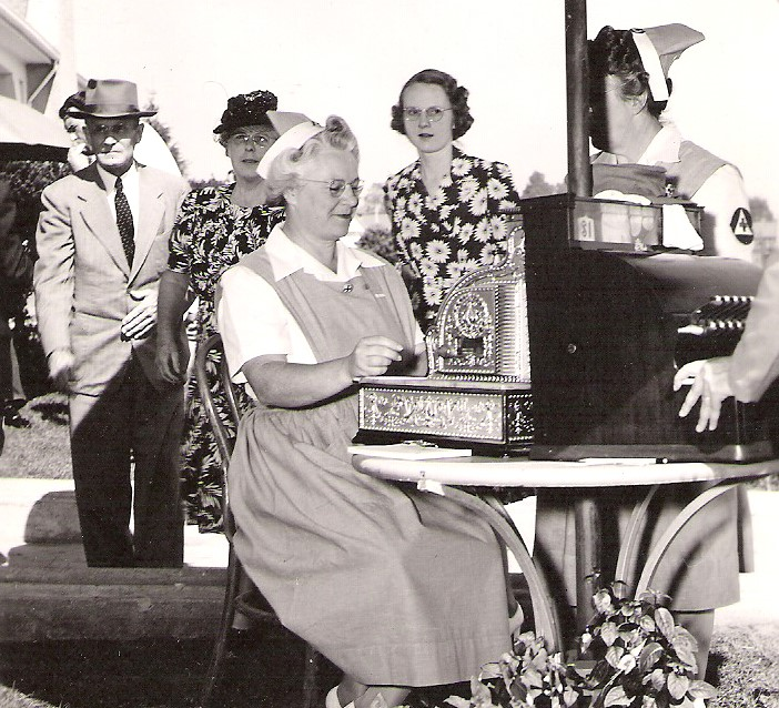 Woman in dress works an old-fashioned cash register.