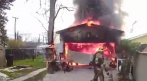Firefighter approaches blazing building.