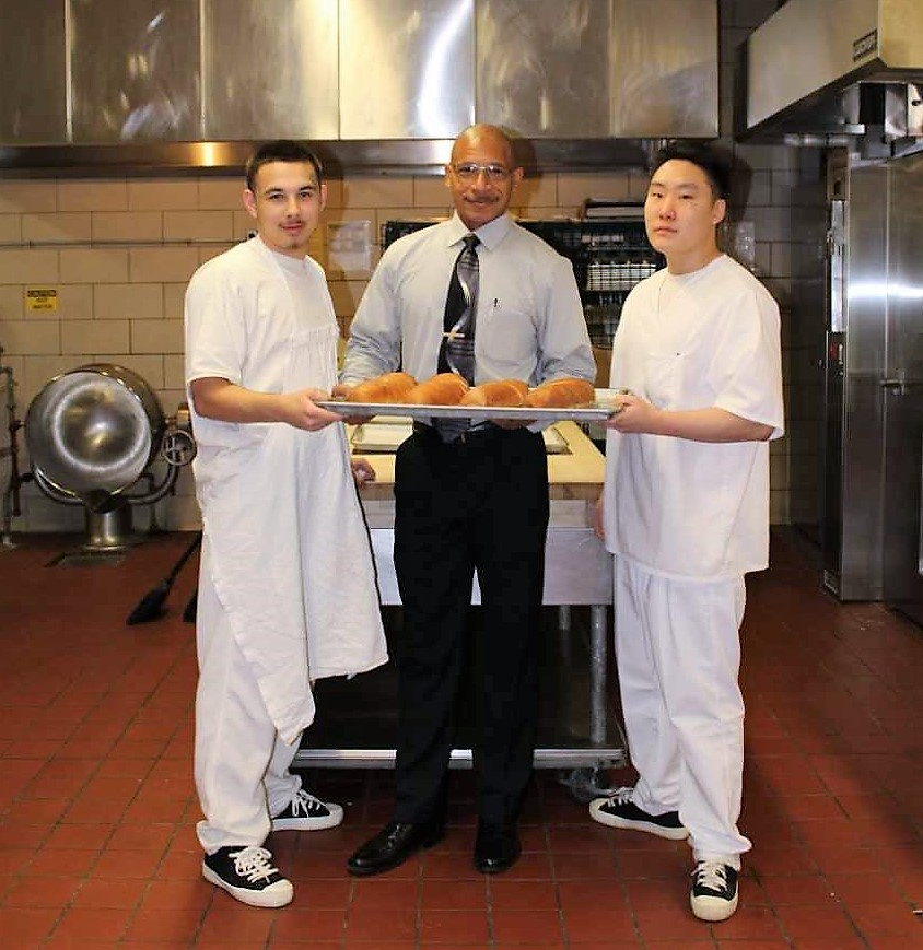 Man wearing tie holds a tray of rolls along with two young men in white clothing. They are standing in a kitchen.