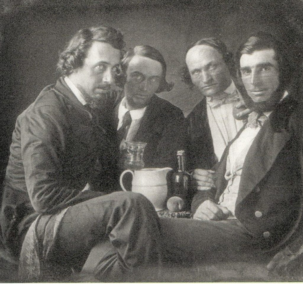 Four men in ties and jackets sit around a peach, bottle and a pitcher.