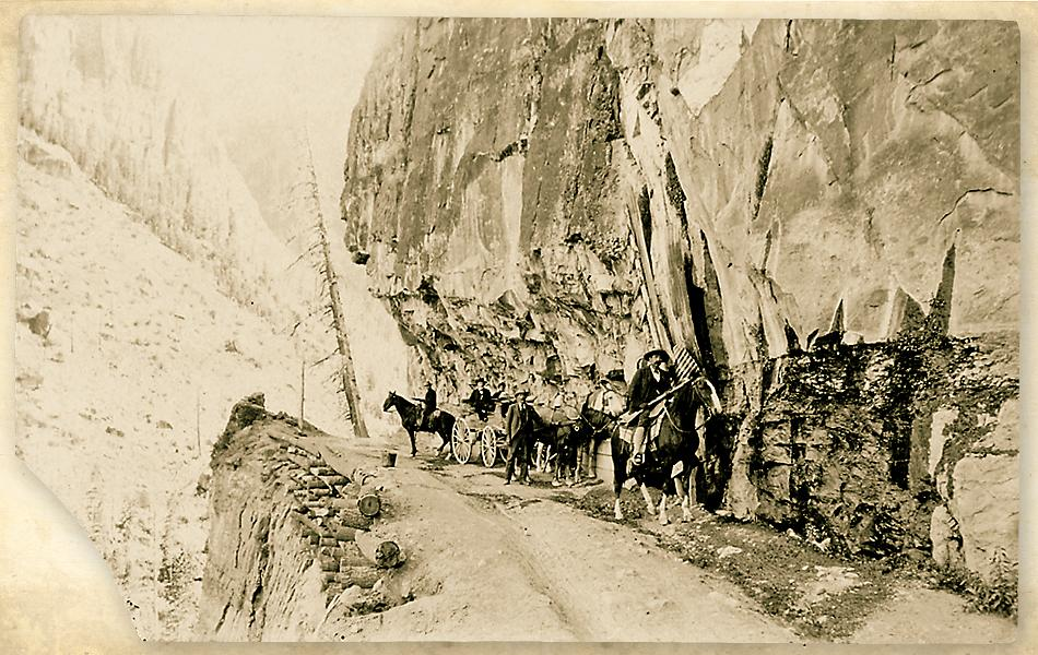 A wagon and a few men on horseback travel on a narrow rough path. San Quentin Captain Estes started his career this way.
