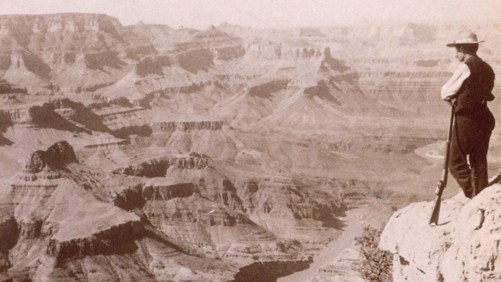 Man leans on rifle, standing on edge of vast canyon. Early guides like Sab Quentin Captain Asa Estes, helped settle the new west.