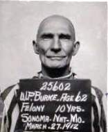 """Bald clean-shaven man in stripes with sign that says """"25602, W.P. Burke, Age 62, Felony 10 yrs., Sonoma, Nat. Mo., March 27, 1912."""""""