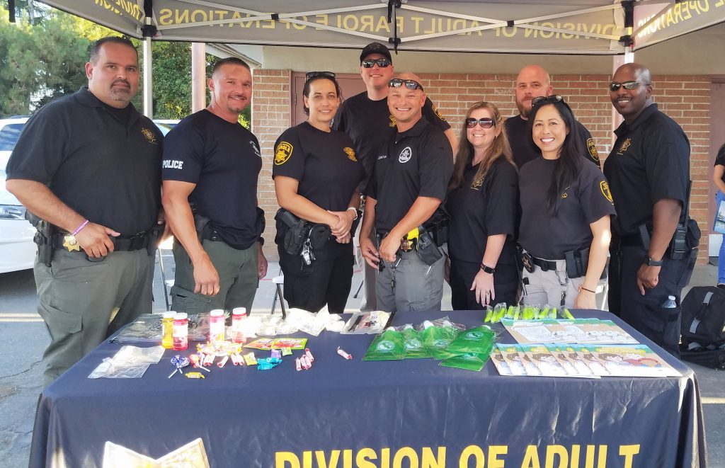 Men in women stand in front of a table that says Division of Adult Parole Operations.