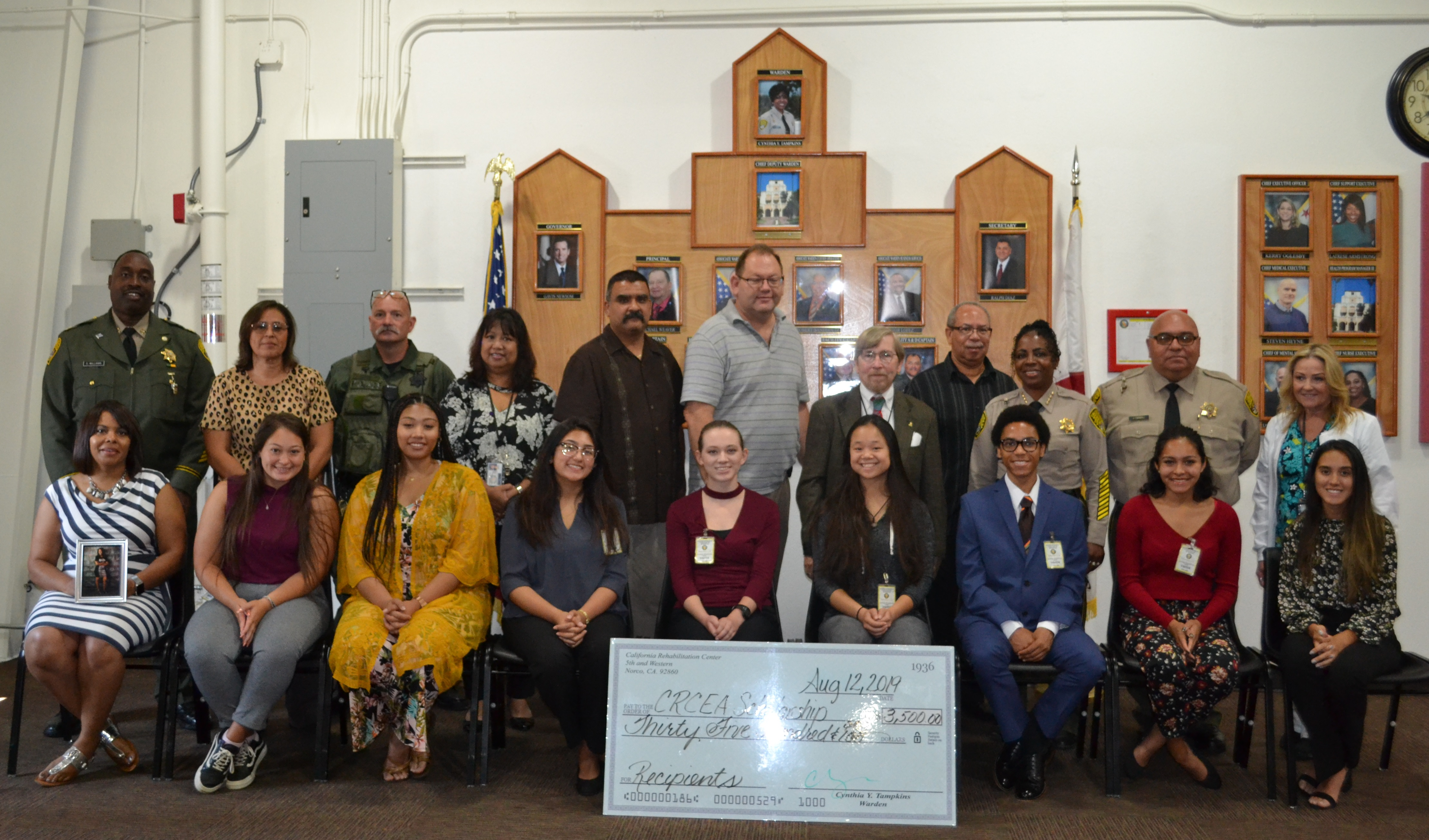 Men and women stand behind an enlarged $3,500 check.