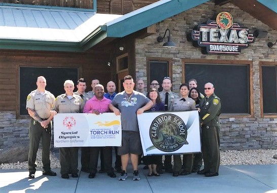 People in uniforms stand with others holding Special Olympics banners in front of a restaurant.