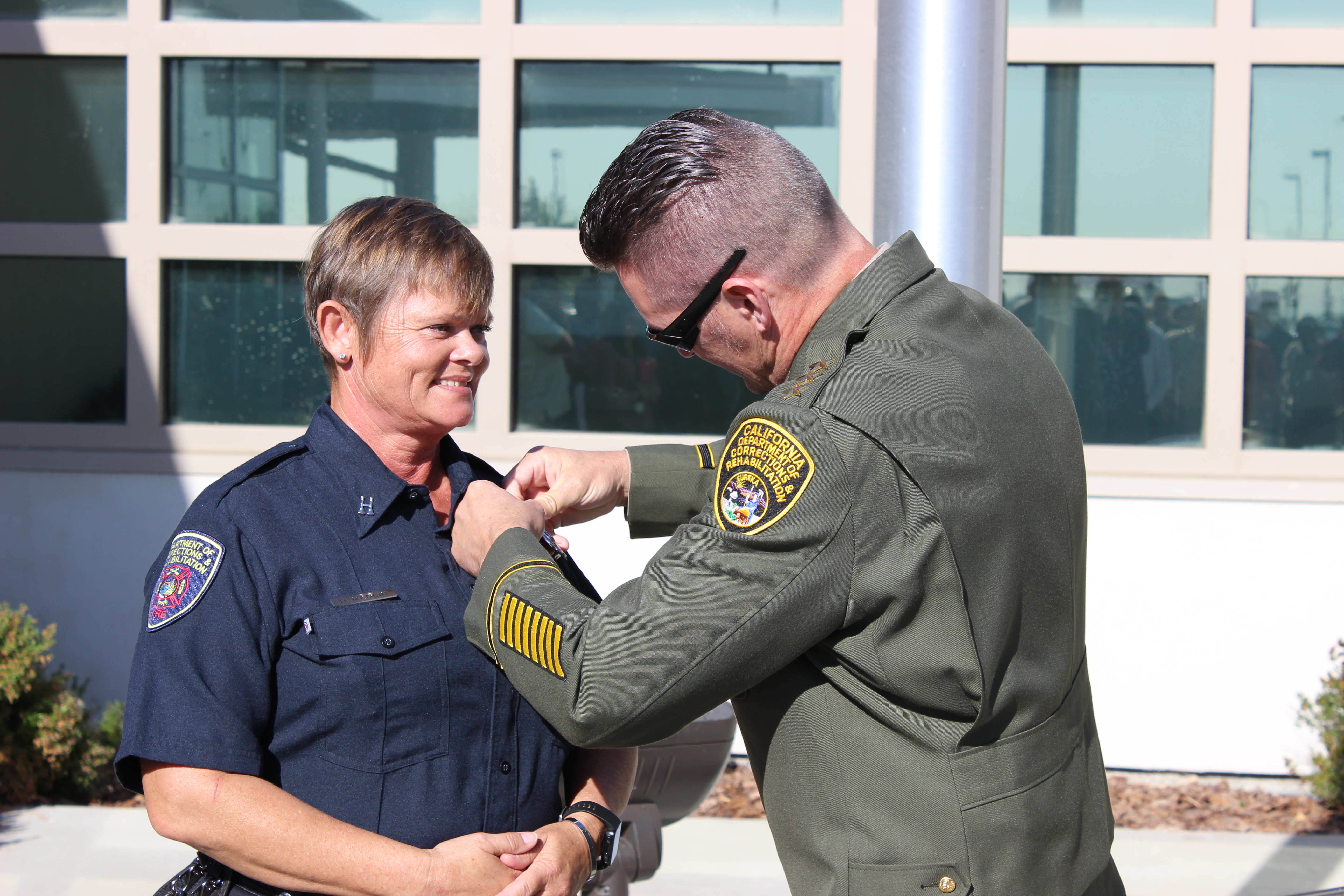 Female in blue uniform is pinned by a man in a correctional uniform.