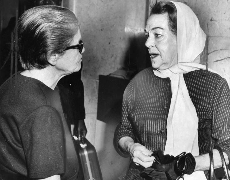 Two older women talk in front of a courthouse.