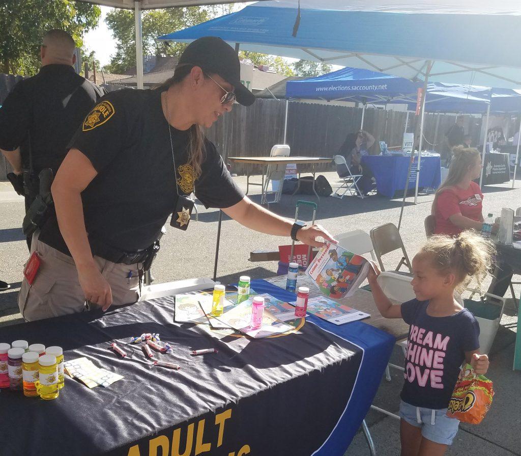 Female parole agent hands a bag to a kid.