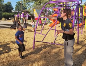 Woman in parole agent uniform plays with a kid at a playground.