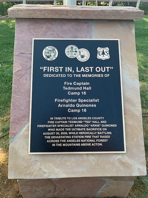 "Plaque with names of fallen firefighters and the words ""Fire In, Last Out."""